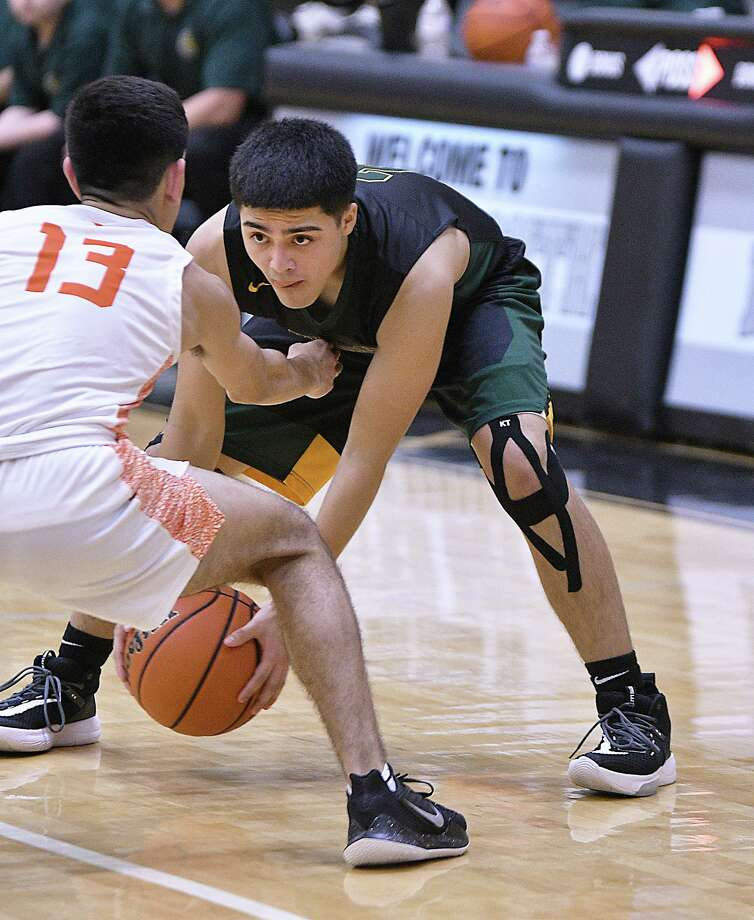 Carlos Puerto defends for the United Longhorns as L.J. Herrera handles the basket for the Nixon Mustangs in the Championship game of the 2019 Border Olympics Boys Basketball Tournament at United South High School, Saturday, December 7, 2019. Photo: Cuate Santos / Laredo Morning Times / Laredo Morning Times