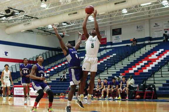 Clear Falls' Corey Kelly (5) muscles up a shot over Houston Northside's Jaylon Travis (4) in the Carlisle-Krueger Classic at Clear Lake High School.