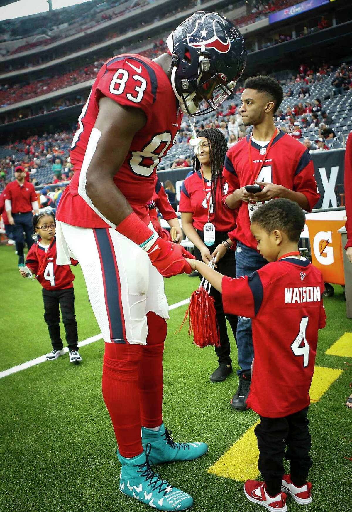 Houston Texans tight end Jordan Thomas (83) greets Daylon Watkins, 7, before an NFL football game against the Denver Broncos at NRG Stadium on Sunday, Dec. 8, 2019, in Houston. Watkins comes to the game through the Make-A-Wish Foundation. Watkins has been diagnosed with Severe Aplastic Anemia and has spent the past couple days visiting the the Texans player during practice and Sunday's game.