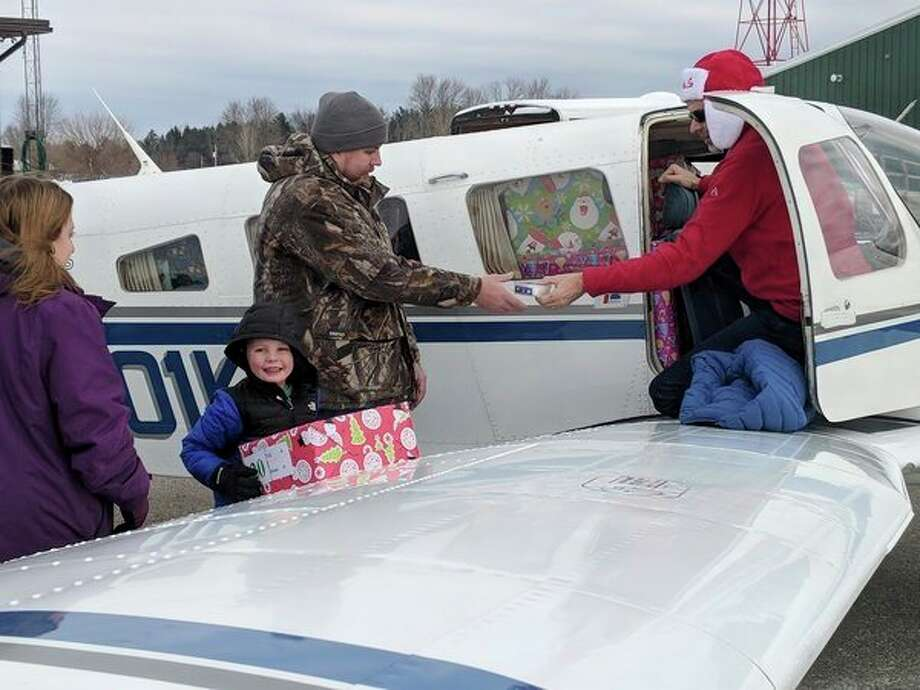 Volunteers received presents for children in group homes and foster care at Gladwin Zettel Memorial Airport Saturday morning as part of Operation Good Chair that assembled in 1971. Planes and trucks filled with presents arrived in many Michigan counties, including Jack Barstow Municipal Airport, where gifts were received for Adoption Option Inc. foster care children. (Tereasa Nims/For the Daily News)