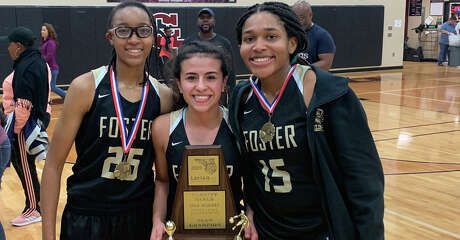 From left to right, Foster girls basketball players  Imani Ivery,  Isabella Babba and      Alicia Blanton pose with the championship trophy from the LCISD tournament on Saturday.