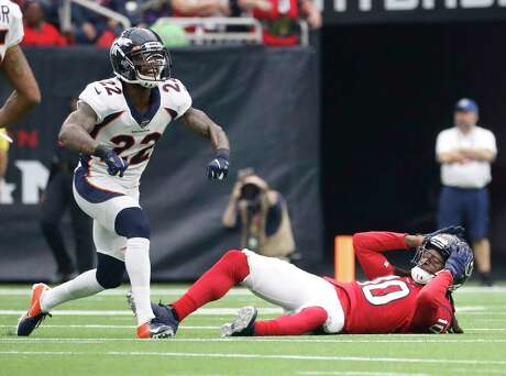 Houston Texans wide receiver DeAndre Hopkins (10) reacts after he was hit hard by Denver Broncos strong safety Kareem Jackson (22) as he went up for a pass during the first half of an NFL football game at NRG Stadium, Sunday, Dec. 8, 2019, in Houston.