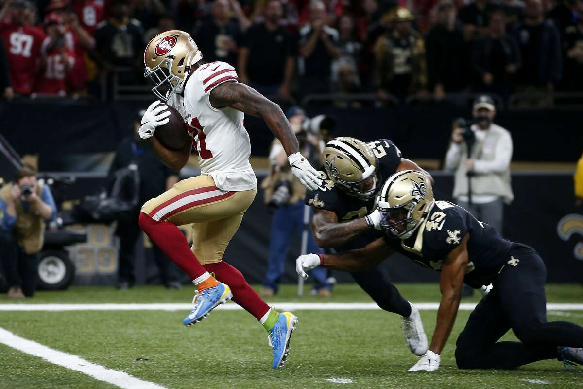 San Francisco 49ers running back Raheem Mostert (31) carries for a touchdown againstNew Orleans Saints free safety Marcus Williams (43) and strong safety Vonn Bell (24) the first half an NFL football game in New Orleans, Sunday, Dec. 8, 2019. (AP Photo/Butch Dill)