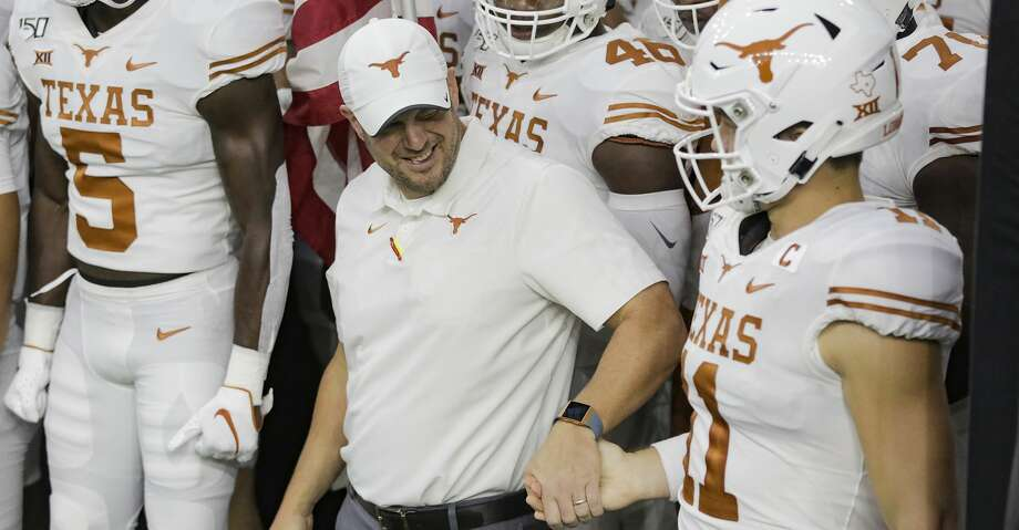 Texas Longhorns head coach Tom Herman shakes hands with Texas Longhorns quarterback Sam Ehlinger (11) before the team takes to the field at NRG Stadium in Houston on Saturday, Sept. 14, 2019. Photo: Elizabeth Conley/Staff Photographer