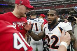 Denver Broncos and former Houston Texans strong safety Kareem Jackson (22) shakes hands with Houston Texans defensive end J.J. Watt long snapper Jon Weeks after an NFL football game at NRG Stadium on Sunday, Dec. 8, 2019, in Houston.