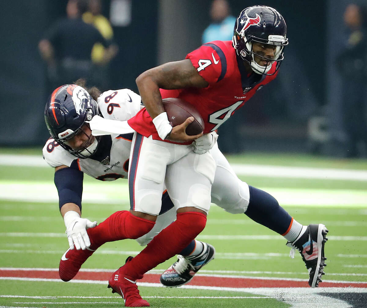 Denver Broncos nose tackle Mike Purcell (98) forces Houston Texans quarterback Deshaun Watson (4) out of the pocket during the fourth quarter of an NFL football game at NRG Stadium on Sunday, Dec. 8, 2019, in Houston.