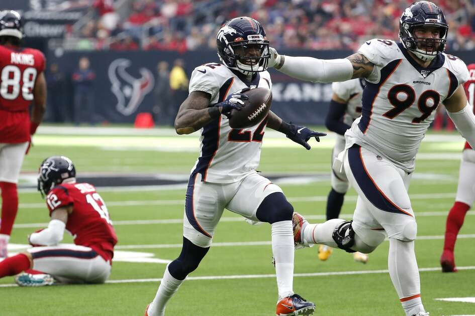 Denver Broncos strong safety Kareem Jackson (22) and Denver Broncos defensive end Adam Gotsis (99) celebrate Jackson's interception of a pass by Houston Texans quarterback Deshaun Watson during the fourth quarter of an NFL football game at NRG Stadium on Sunday, Dec. 8, 2019, in Houston.