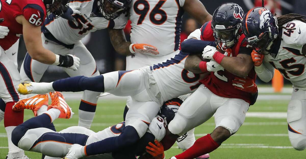 Houston Texans running back Carlos Hyde (23) fights for yardage against the Denver Broncos defense during the second quarter of an NFL football game at NRG Stadium on Sunday, Dec. 8, 2019, in Houston.