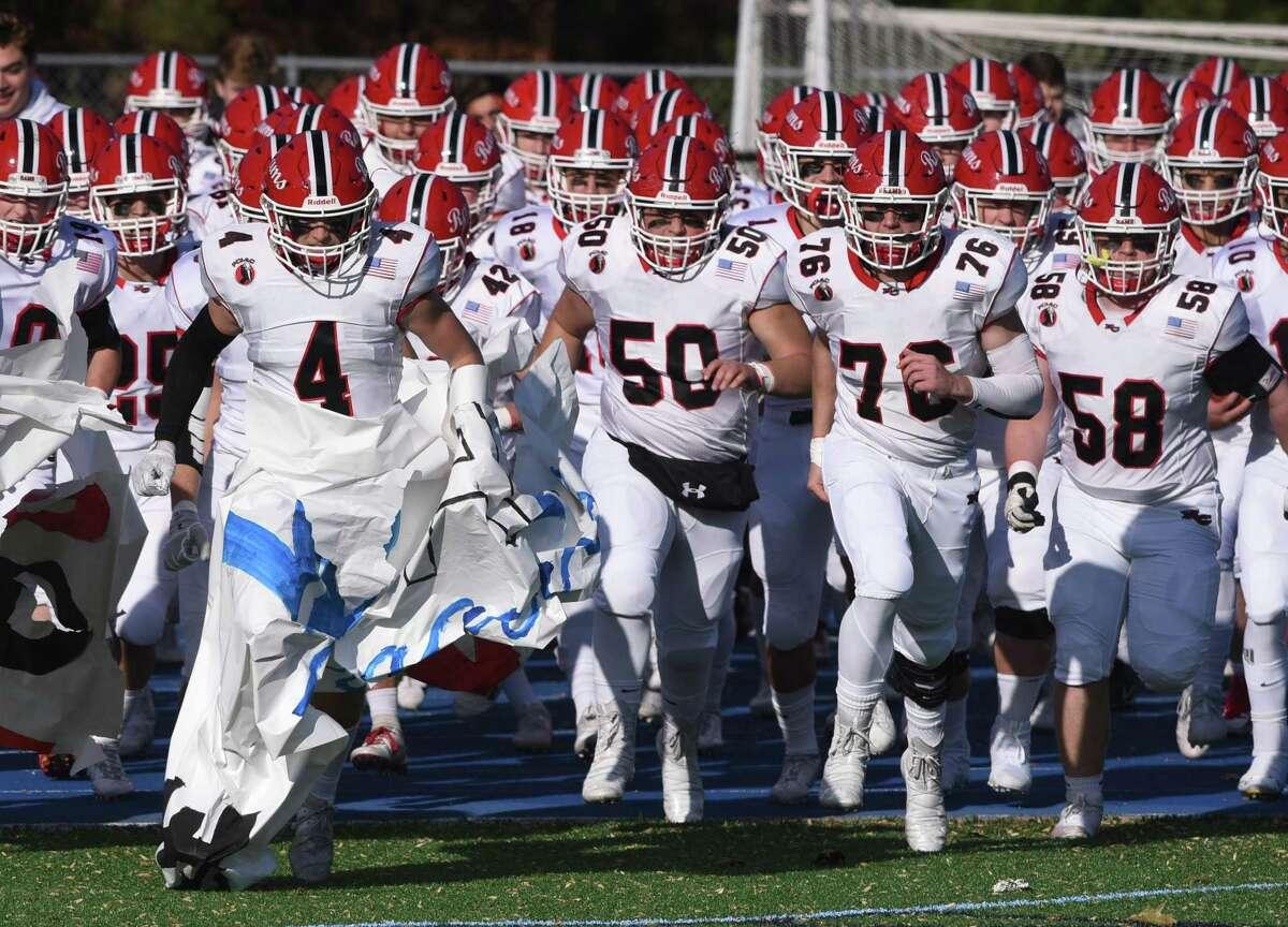 New Canaan senior co-captains Drew Guida (4) and Matt Rigione (76) help lead the Rams' football team onto the field for the annual Turkey Bowl against Darien at Darien High School on Thursday, Nov. 28, 2019