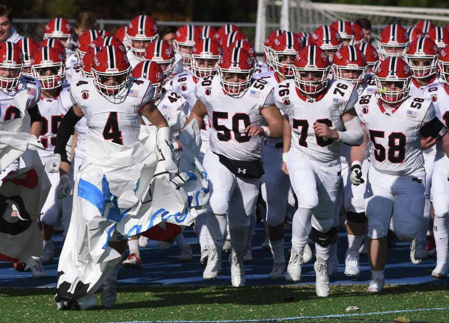 New Canaan senior co-captains Drew Guida (4) and Matt Rigione (76) help lead the Rams' football team onto the field for the annual Turkey Bowl against Darien at Darien High School on Thursday, Nov. 28, 2019 Photo: Dave Stewart / Hearst Connecticut Media / Hearst Connecticut Media