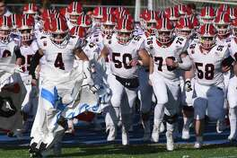 New Canaan senior co-captains Drew Guida (4) and Matt Rigione (76) help lead the Rams' football team onto the field for the annual Turkey Bowl against Darien at Darien High School on Thursday, Nov. 28, 2019