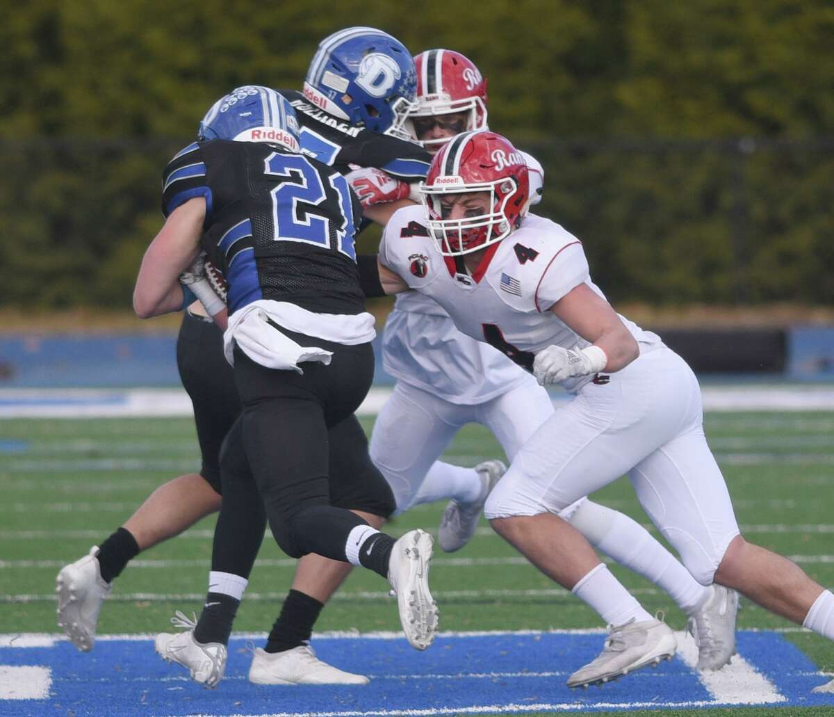 New Canaan's Drew Guida (4) catches up to Darien's Will Kirby (21) during the annuual Turkey Bowl football game at Darien High School on Thursday, Nov. 28, 2019.