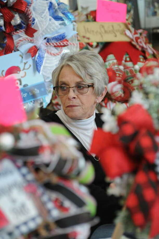 Linda Wilson, of Staunton, looks out from her booth, Wreaths by Linda Marie, at the Olde Alton Arts and Crafts Fair. Photo: David Blanchette|For The Telegraph