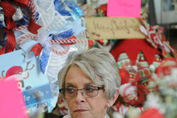 Linda Wilson, of Staunton, looks out from her booth, Wreaths by Linda Marie, at the Olde Alton Arts and Crafts Fair.
