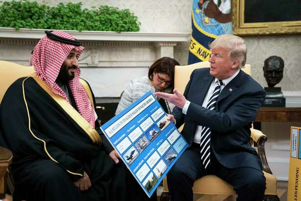 President Donald Trump shows off posters as he talks with Saudi Crown Prince Mohammed bin Salman in March 2018.