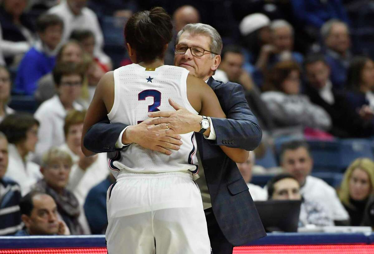 UConn coach Geno Auriemma hugs Connecticut's Megan Walker in the second half of Sunday's win over rival Notre Dame in Storrs.