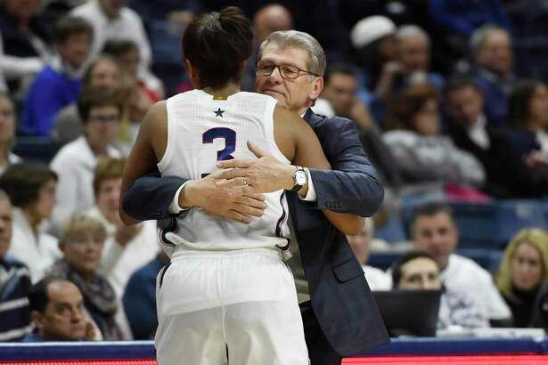 Coach Geno Auriemma hugs Connecticut's Megan Walker in the second half of an NCAA women's basketball game, Sunday, Dec. 8, 2019, in Storrs, Conn.