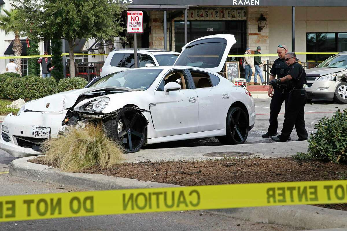 San Antonio Police personnel investigate the scene of a shooting at The Rim Shopping Center, Sunday, Dec. 8, 2019. According to police, a father and his son were shot while in their vehicle.