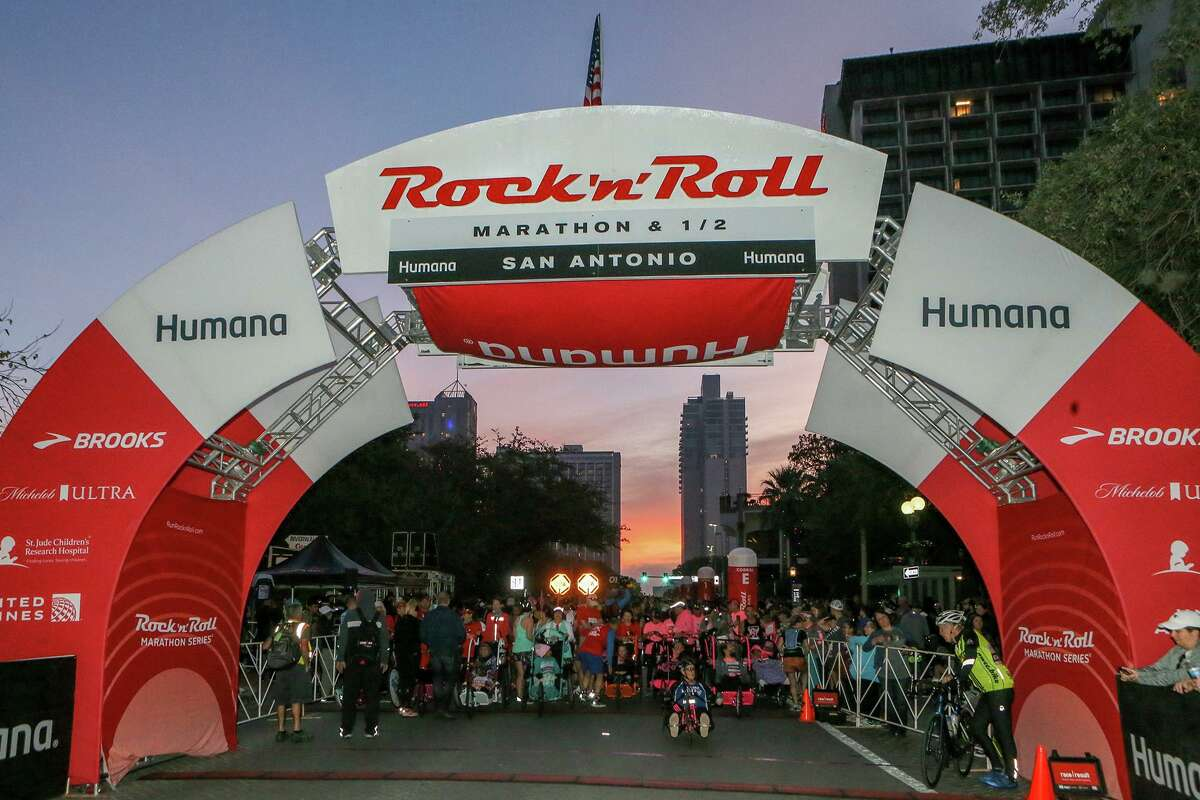 The sun begins to rise in the East as competitors prepare to take off from the starting line of the Rock 'n' Roll San Antonio Marathon on West Market Street on Sunday, Dec. 8, 2019.