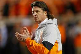 """STILLWATER, OK - NOVEMBER 30: Head coach Mike Gundy of the Oklahoma State Cowboys encourages his team before a """"Bedlam"""" game against the Oklahoma Sooners on November 30, 2019 at Boone Pickens Stadium in Stillwater, Oklahoma. (Photo by Brian Bahr/Getty Images)"""