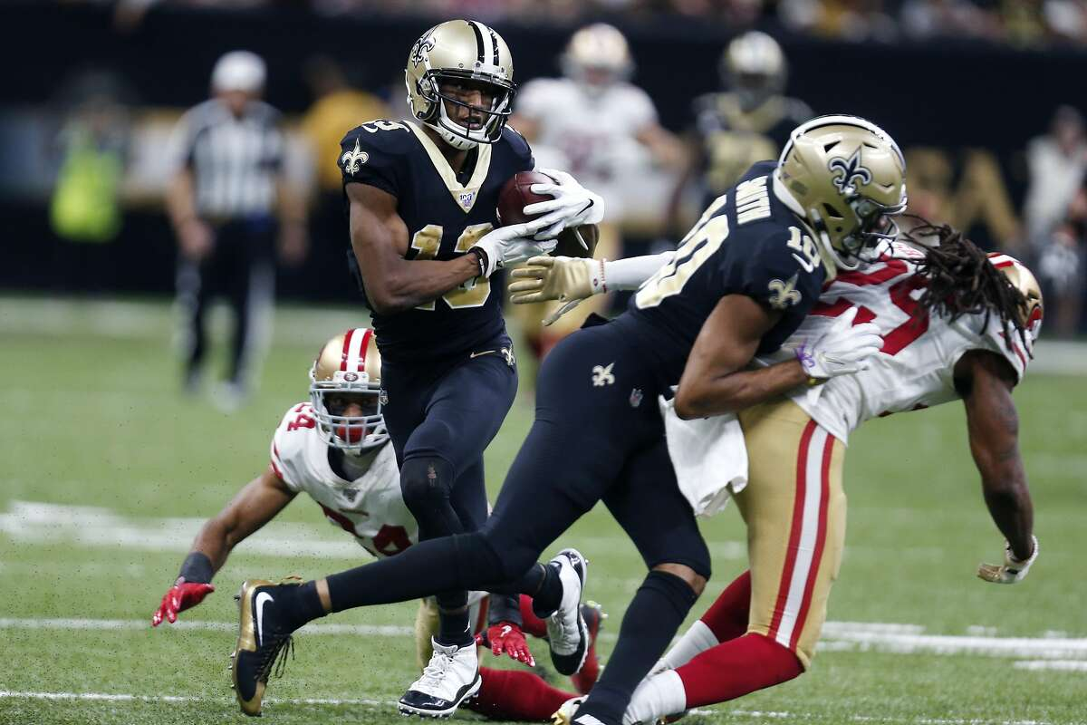 New Orleans Saints wide receiver Michael Thomas (13) carries for a touchdown as wide receiver Tre'Quan Smith (10) blocks San Francisco 49ers strong safety Jaquiski Tartt (29) in the second half an NFL football game in New Orleans, Sunday, Dec. 8, 2019. (AP Photo/Butch Dill)