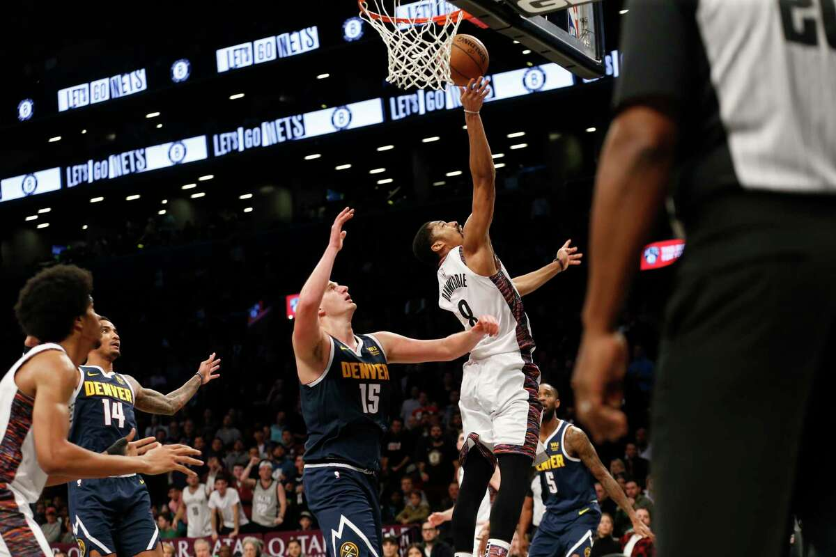 Brooklyn Nets guard Spencer Dinwiddie (8) puts up a shot against Denver Nuggets center Nikola Jokic (15) during the second half of an NBA basketball game on Sunday, Dec. 8, 2019, in New York. The Nets won 105-102. (AP Photo/Nicole Sweet)