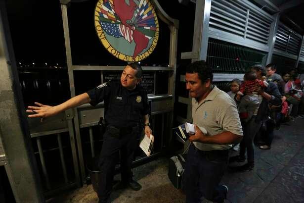 """En esta fotografía de archivo del 17 de septiembre de 2019, un oficial de Aduanas y Protección Fronteriza da indicaciones a una familia migrante originaria de Nicaragua, quienes están solicitando asilo a los Estados Unidos en el Puente Internacional I de Nuevo Laredo, México, hacia Laredo, Texas, para que se entreviste con oficiales de inmigración. Estados Unidos ha fijado un límite a los solicitantes de asilo, la política conocida como """"permanecer en México"""" ha devuleto a más de 55.000 solicitantes de asilo a México."""