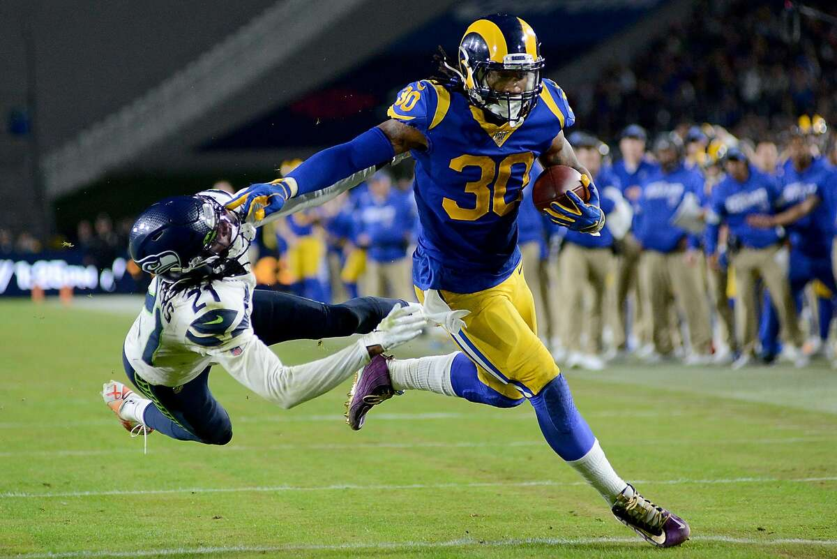 LOS ANGELES, CALIFORNIA - DECEMBER 08: Running back Todd Gurley #30 of the Los Angeles Rams stiff arms cornerback Tre Flowers #21 of the Seattle Seahawks on his way to a touchdown in the fourth quarter of the game at Los Angeles Memorial Coliseum on December 08, 2019 in Los Angeles, California. (Photo by Meg Oliphant/Getty Images)