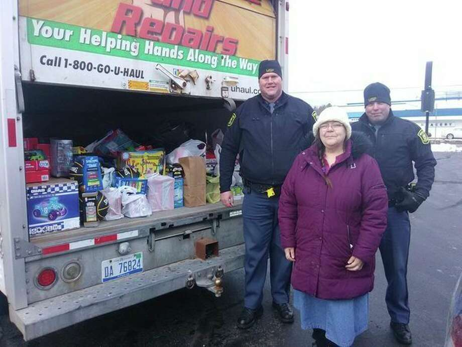 MSP troopersDavid Skorka and Chris Ingalls present a truck loaded with donated items to Lisa Clarke of ECHO His Love. (Courtesy photo)