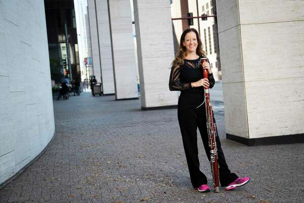 Elise Wagner holds her bassoon while wearing her running shoes by the Jesse H. Jones Hall for the Performing Arts on Wednesday, Nov. 6, 2019, in Houston. Wagner, who is also a runner, has been a member of the Houston Symphony bassoon section since September 2008. Wagner focuses in exercising because it's important for her breathing, and overall core support, which makes her a better musician.