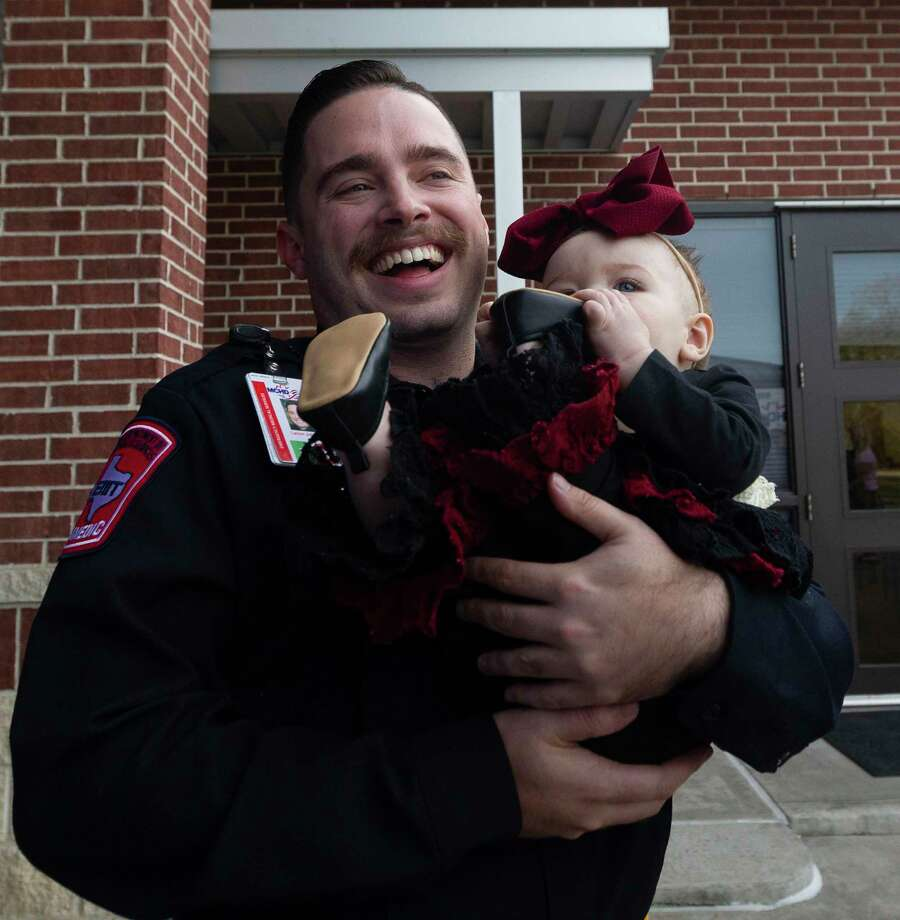Montgomery County Hospital District paramedic Larson Johnson shares a laugh as he holds eight-month-old Khloe Mock during a visit to Montgomery Fire Station 51, Wednesday, Dec. 4, 2019, in Montgomery. Firefighters from Station 51 and MCHD paramedics reunited with Mock and her family after they helped her mother, Lindey, deliver Khloe in the back of her SUV while traveling on Texas-105 back on March 22. Photo: Jason Fochtman, Houston Chronicle / Staff Photographer / Houston Chronicle