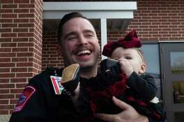 Montgomery County Hospital District paramedic Larson Johnson shares a laugh as he holds eight-month-old Khloe Mock during a visit to Montgomery Fire Station 51, Wednesday, Dec. 4, 2019, in Montgomery. Firefighters from Station 51 and MCHD paramedics reunited with Mock and her family after they helped her mother, Lindey, deliver Khloe in the back of her SUV while traveling on Texas-105 back on March 22.