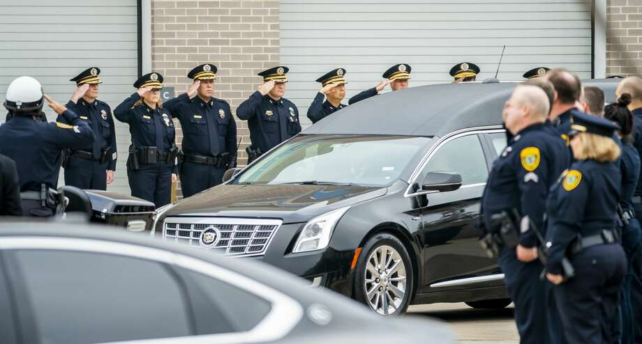 Commanders and officers from the Houston Police Department salute as the body of Sgt. Christopher Brewster is brought out of the Harris County Institute of Forensic Sciences building to be escorted to a funeral home in preparation for Wednesday's planned visitation and a funeral planned for Thursday, in Houston, Monday, Dec. 9, 2019. Photo: Mark Mulligan/Staff Photographer
