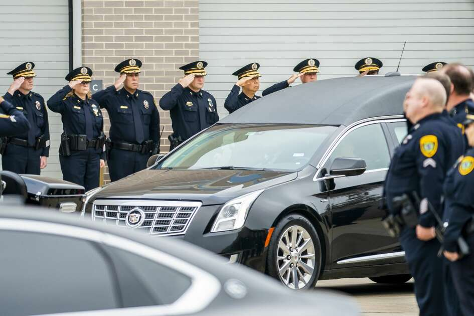 Commanders and officers from the Houston Police Department salute as the body of Sgt. Christopher Brewster is brought out of the Harris County Institute of Forensic Sciences building to be escorted to a funeral home in preparation for Wednesday's planned visitation and a funeral planned for Thursday, in Houston, Monday, Dec. 9, 2019.