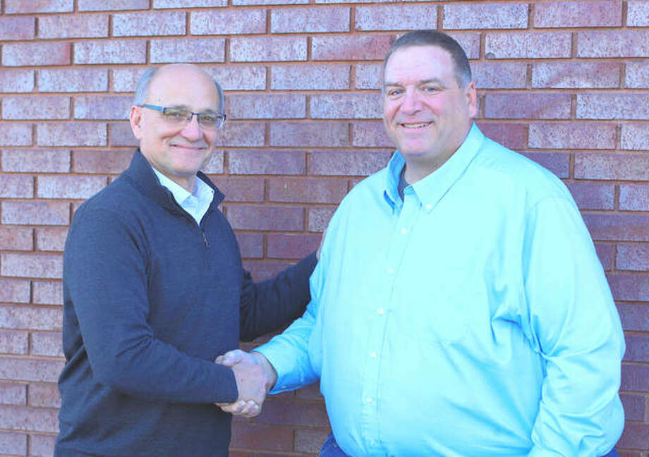 Mark Schaefer, President/CEO of Jersey State Bank, congratulates Thomas Schnelt on becoming Vice President of Lending.