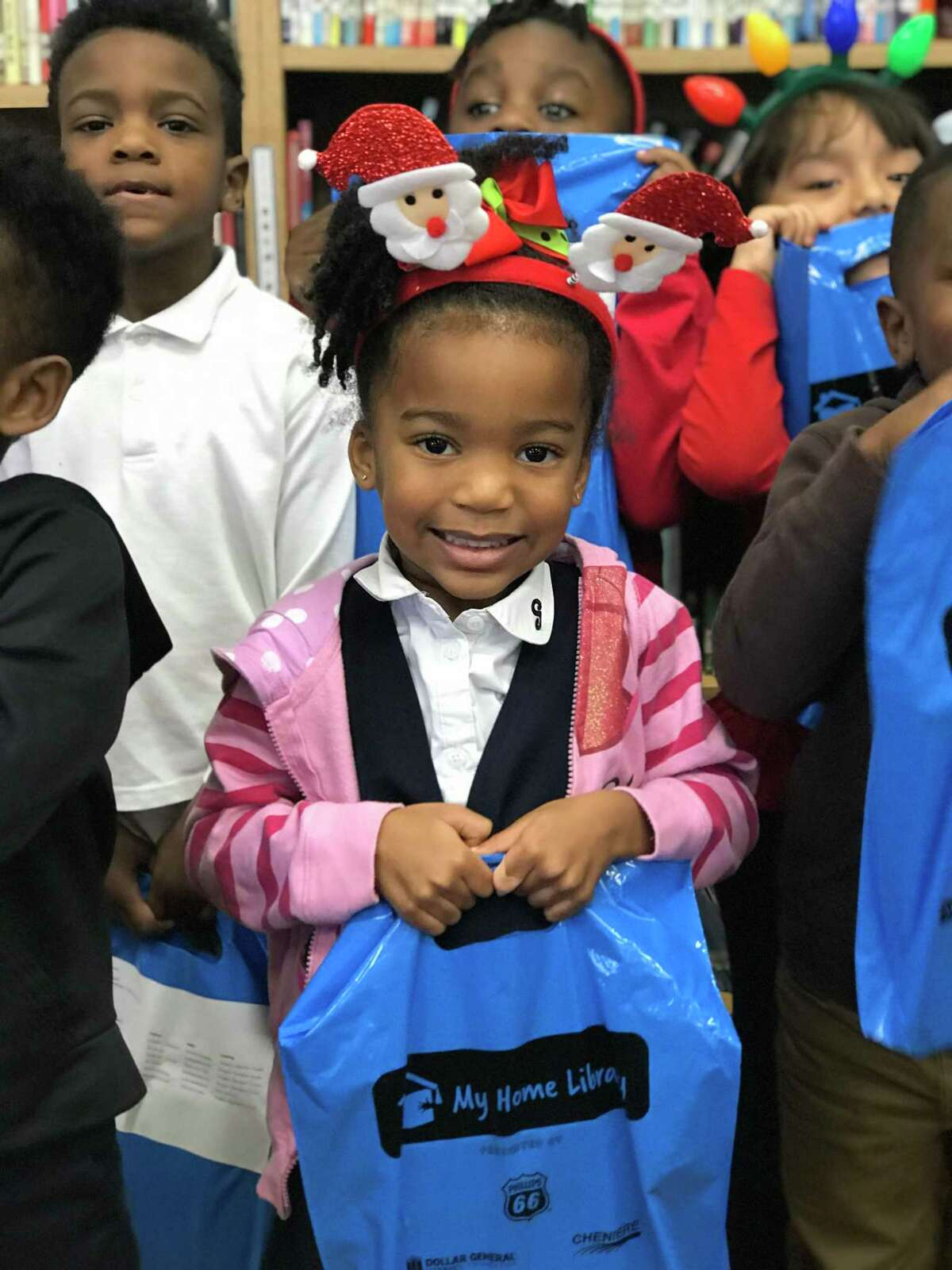 A child proudly carries her bag of six books she received from the Barbara Bush Houston Literacy Foundation My Home Library program.