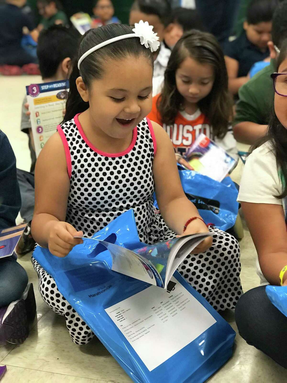 A child lights up as she receives a bag with six books she chose from the Barbara Bush Houston Literacy Foundation My Home Library program.