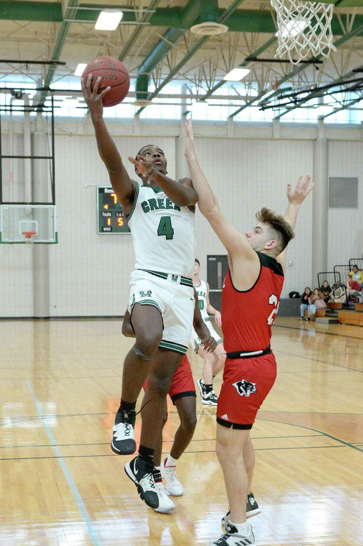 Rommell Williams (4) of Mayde Creek drives past Spencer Skivington (21) of Tomball during pool play of the Katy Classic Basketball Tournament between the Mayde Creek Rams and the Tomball Cougars on Thursday, December 5, 2019 at Mayde Creek HS, Houston, TX.