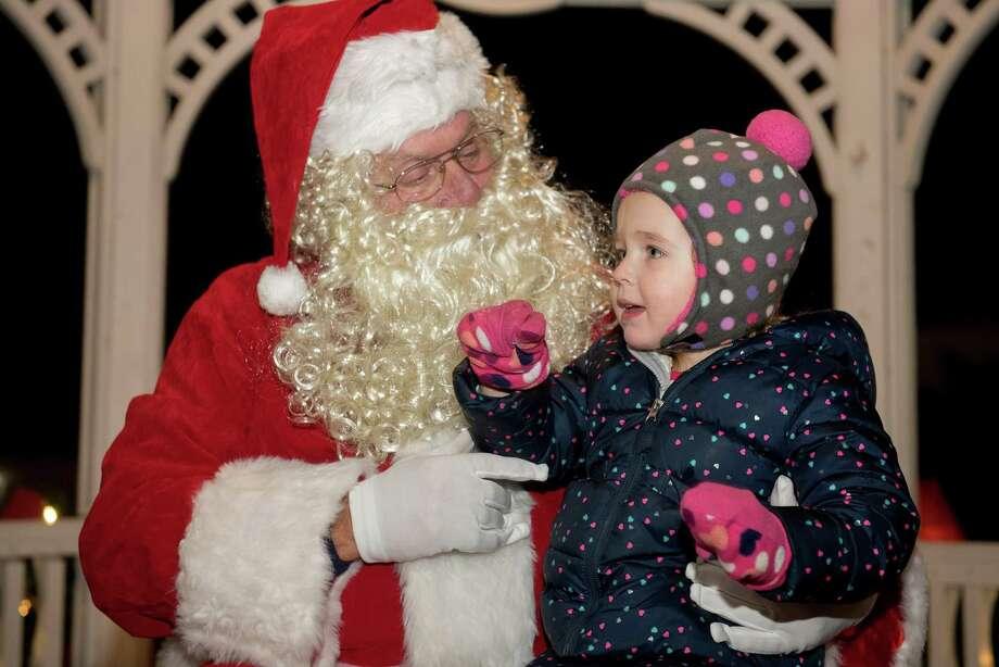 Amelia Sclafani, 3, of Wilton lets Santa know what she wants for Christmas. Photo: Bryan Haeffele / Hearst Connecticut Media / Hearst Connecticut Media