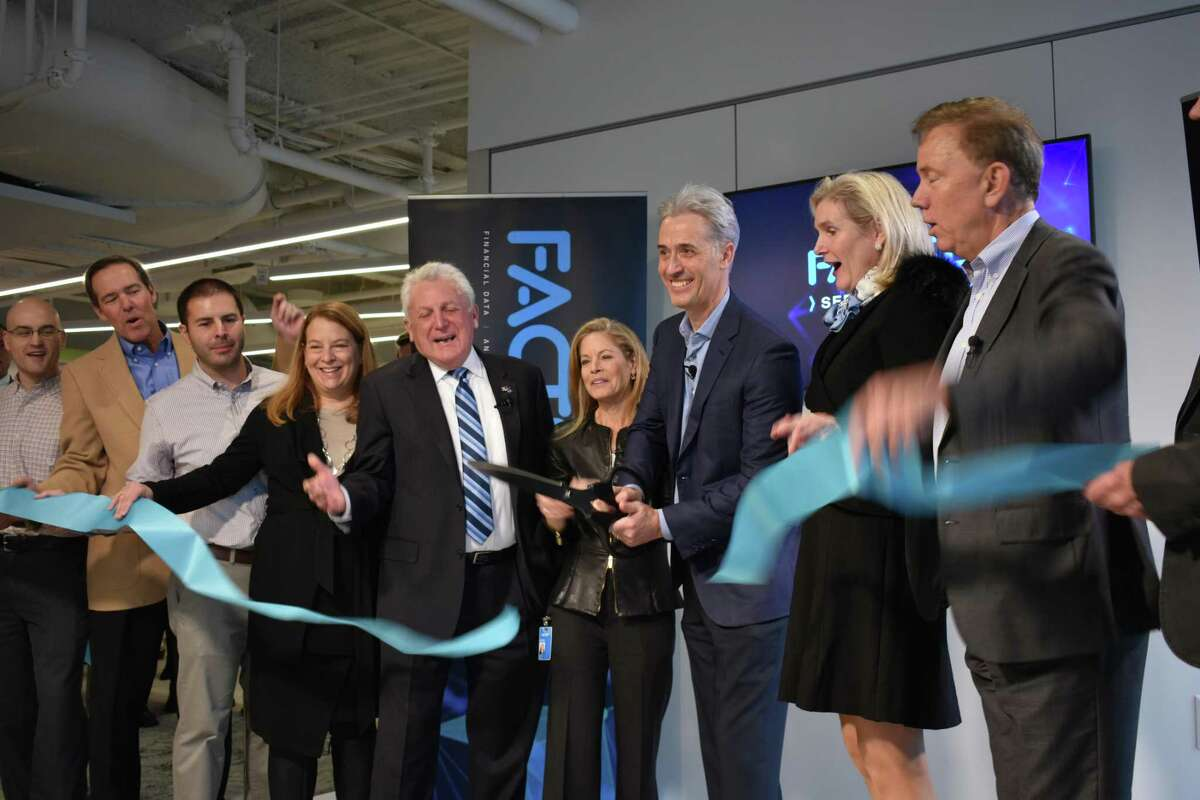 FactSet CEO Phil Snow cuts the ribbon in a ceremony marking the company moving into a new headquarters office at 45 Glover Ave. in Norwalk, Conn., with officials on hand including Gov. Ned Lamont (right) and Norwalk Mayor Harry Rilling (center).
