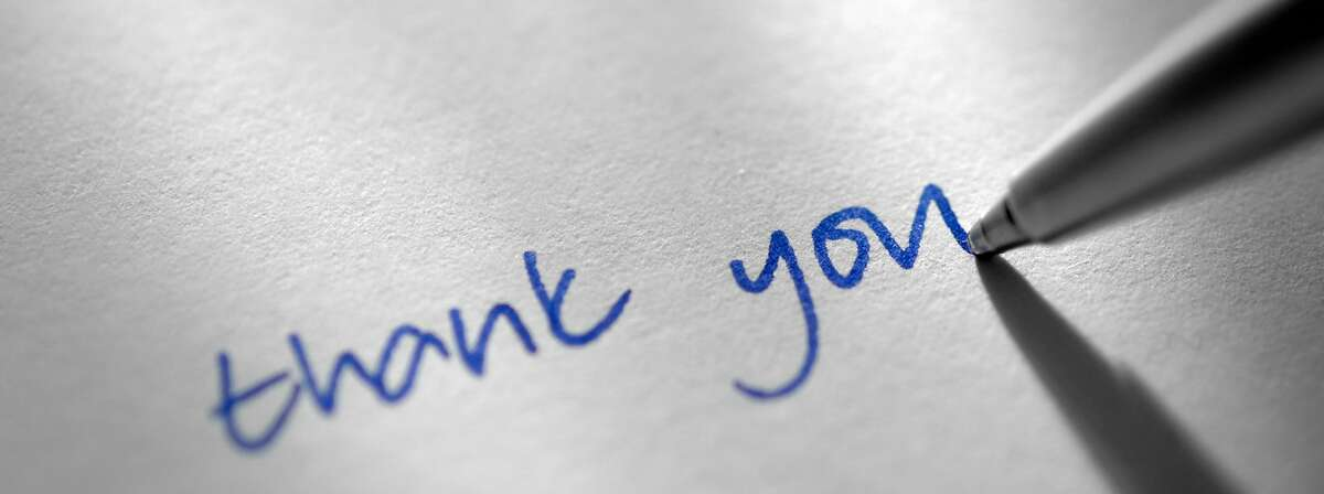 Photo illustration of silver ballpoint pen writing the words thank you.