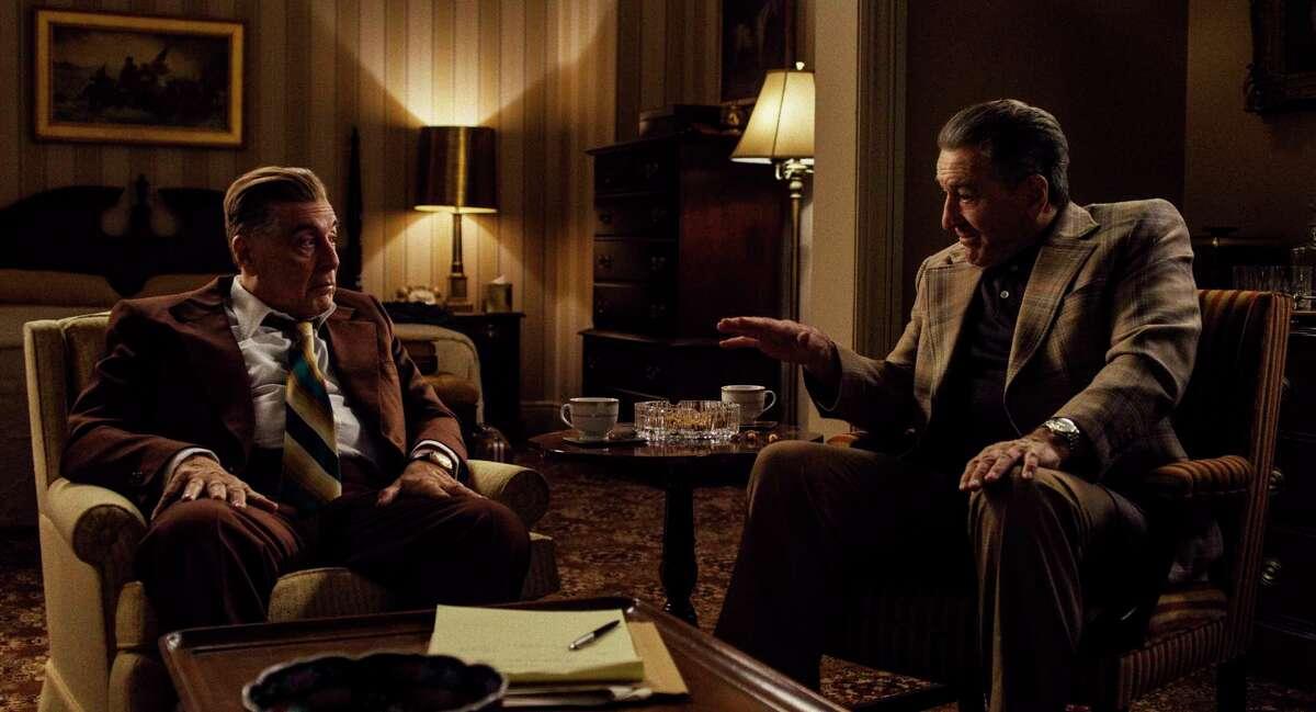 "This image released by Netflix shows Al Pacino portraying Jimmy Hoffa, left, and Robert De Niro as Frank Sheeran in a scene from ""The Irishman.""(Netflix via AP)"