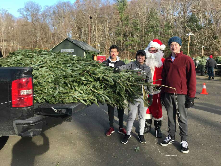 New Canaan High School Service League of Boys (SLOBs) members Ben Apicella, Payton Welch and Johnny Maechling lend Santa a hand at the Exchange Club's 52nd annual Christmas Tree sale at Kiwanis Park. Photo: Contributed Photo