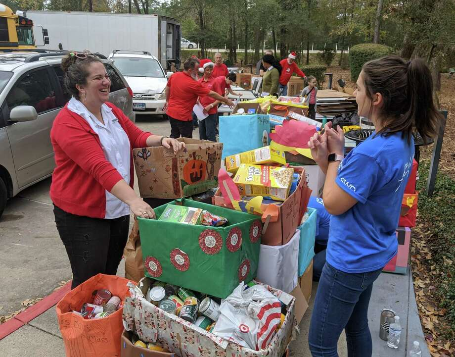 Faith Lane, Director of Programs for the Montgomery County Food Bank, and Natalie Lanclos, a volunteer from Southwest Energy, help organize the donations for this year's holiday food drive for the food bank. Photo: Jamie Swinnerton