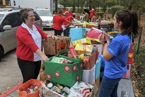 Faith Lane, Director of Programs for the Montgomery County Food Bank, and Natalie Lanclos, a volunteer from Southwest Energy, help organize the donations for this year's holiday food drive for the food bank.
