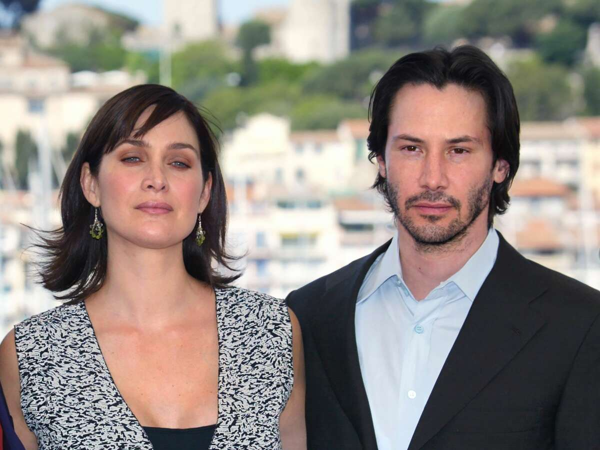 US actor Keanu Reeves and Canadian-born actress Carrie-Anne Moss pose for photographers on a terrace of the Palais des festivals during the photocall for
