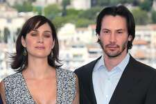 """US actor Keanu Reeves and Canadian-born actress Carrie-Anne Moss pose for photographers on a terrace of the Palais des festivals during the photocall for """"Matrix Reloaded"""" directed by the Wachowski brothers during the 56th Cannes film festival on 15 May 2003. - Sci-fi franchise """"The Matrix"""" will return for a fourth film with Keanu Reeves reprising his role as kung fu-kicking, shades-wearing hero Neo, studio Warner Bros said Tuesday. Lana Wachowski will helm the project, returning to write, direct and produce the latest installment of the hugely popular series about humans trapped in a virtual reality by machines, which has netted more than $1.6 billion worldwide. (Photo by FRANCOIS GUILLOT / AFP) / ALTERNATIVE CROP (Photo credit should read FRANCOIS GUILLOT/AFP via Getty Images)"""