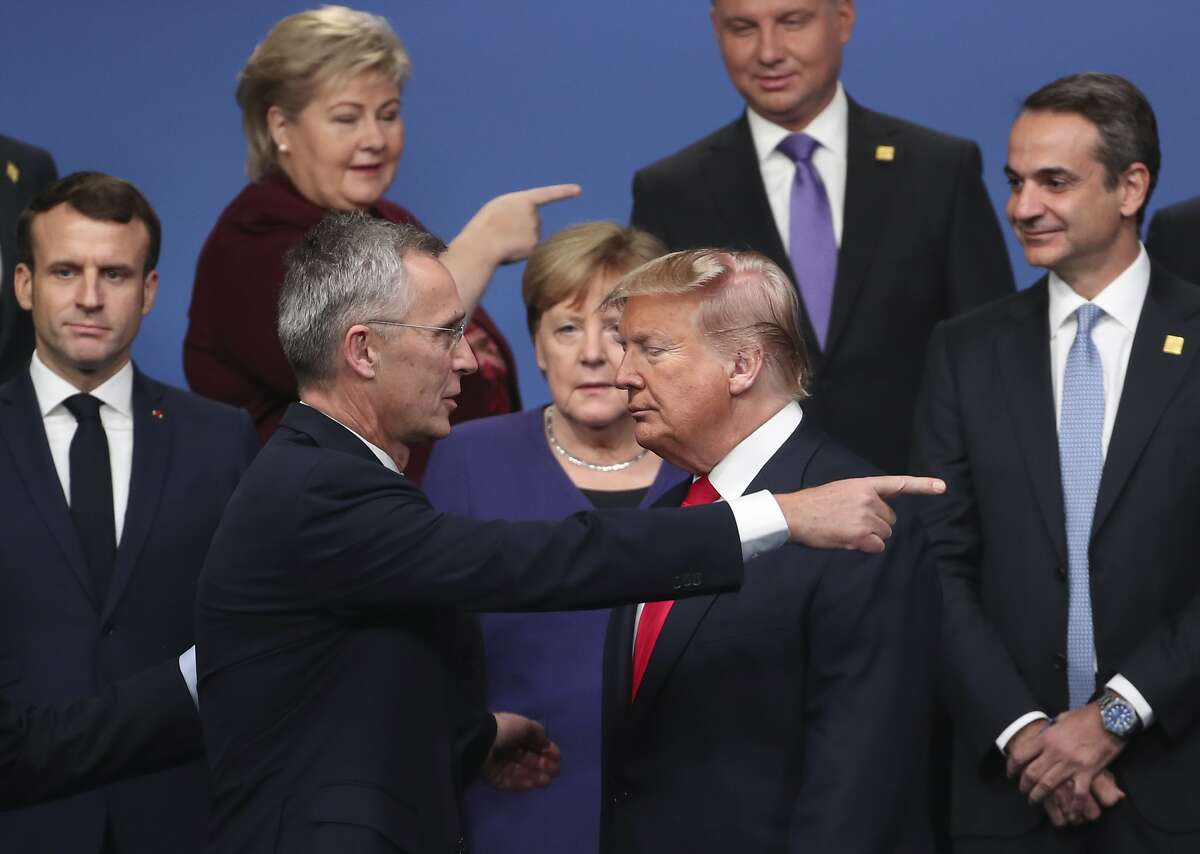 NATO Secretary General Jens Stoltenberg, center front left, speaks with U.S. President Donald Trump, center front right, after a group photo at a NATO leaders meeting at The Grove hotel and resort in Watford, Hertfordshire, England, Wednesday, Dec. 4, 2019. NATO Secretary-General Jens Stoltenberg rejected Wednesday French criticism that the military alliance is suffering from brain death, and insisted that the organization is adapting to modern challenges. From left, French President Emmanuel Macron, Norway's Prime Minister Erna Solberg, German Chancellor Angela Merkel, Poland's President Andrzej Duda and Greek Prime Minister Kyriakos Mitsotakis. (AP Photo/Francisco Seco)