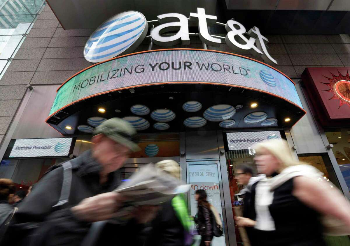 In this Oct. 21, 2014 photo, people pass an AT&T store in New York's Times Square. AT&T is being sued by the government over allegations it misled millions of smartphone customers who were promised unlimited data but had their Internet speeds cut by the company - slowing their ability to open web pages or watch streaming video. (AP Photo/Richard Drew)