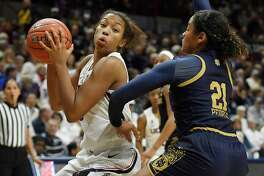 UConn's Megan Walker, left, is guarded by Notre Dame's Anaya Peoples, right, during the second half on Sunday in Storrs.